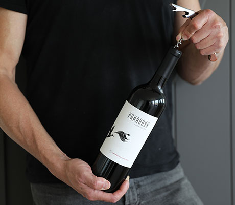 A male holding a bottle of Paraduxx red wine