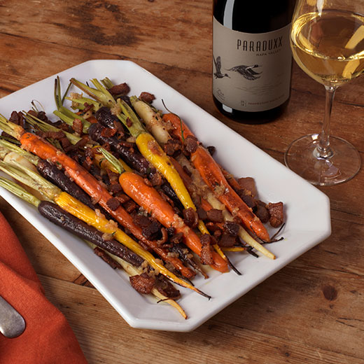 Roasted rainbow carrots with a glass of Paraduxx white wine blend