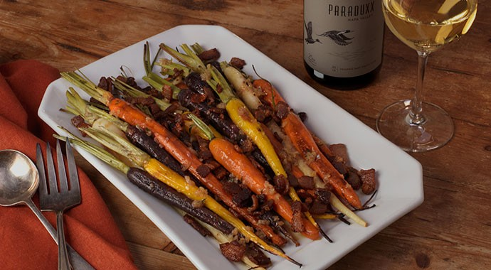 Roasted Rainbow Carrots with Shallot Vinaigrette and Crispy Bacon and a white wine glass